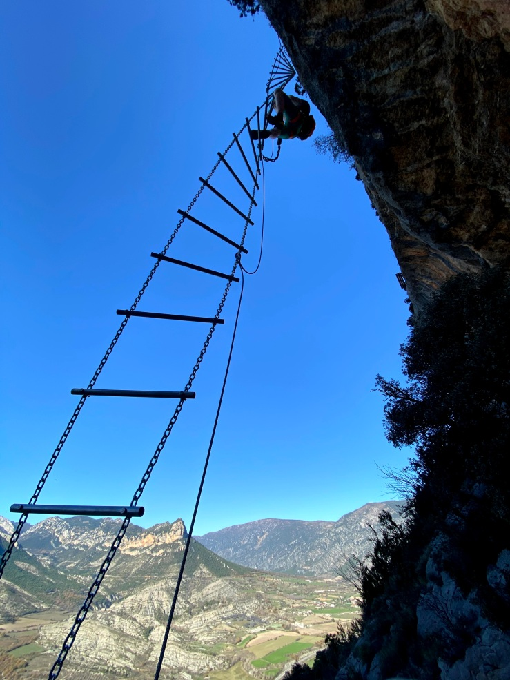 Climber in scaling a twisting via ferrata ladder with the pre-pyrenees in the background