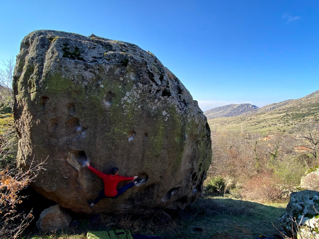 Climber spread wide on a problem at Dabnica between two small huecos with a heel hook matching one hand.
