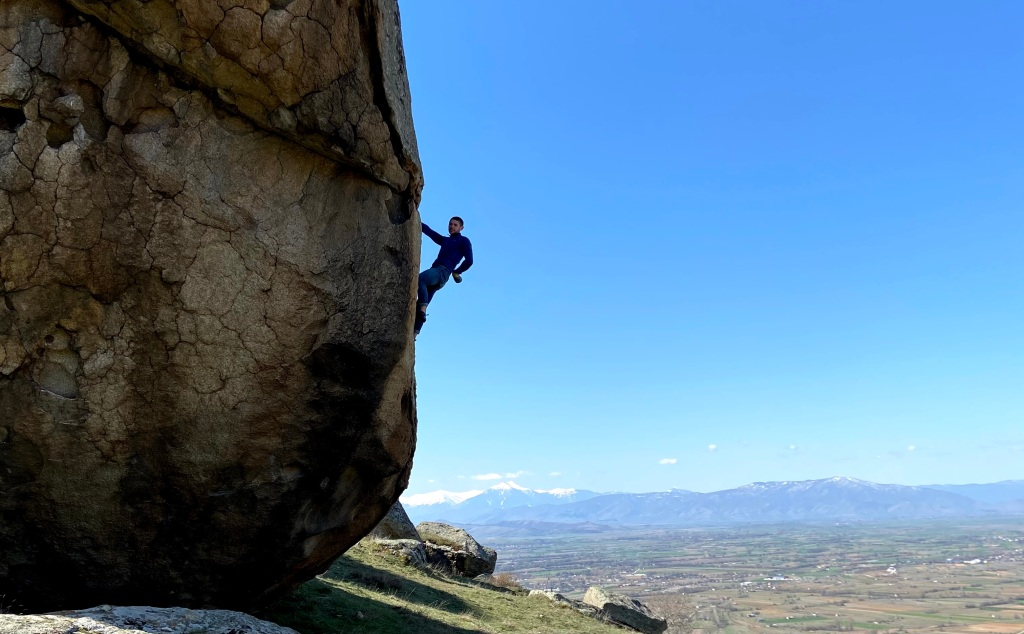 Climber on a highball boulder chalking one hand. There are some flat planes, then with some snowy mountains in the background