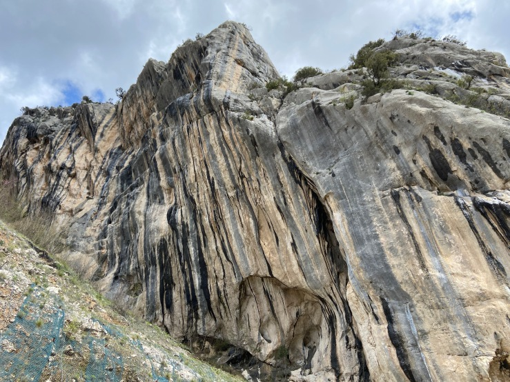 Imposing crag with wet, grey and white limestone streaks.