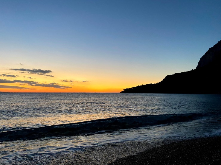 Orange sunrise with the waves lapping  at Olympos beach.