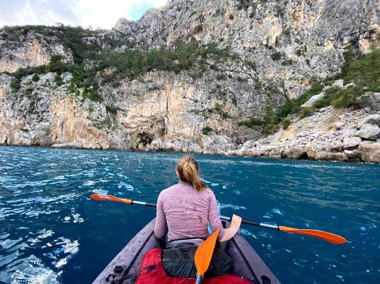 Woman paddling in sea kayak to Ceneviz. The rock is towering above.