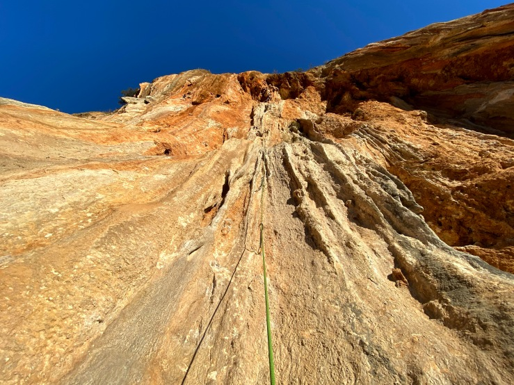Orange limestone wall of Sarkit sector dripping with tufas. Climber is half way up JaJa City.