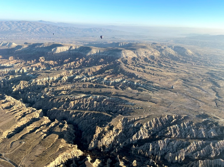 Aerial view from the hot air ballon down on the valleys of Cappadocia. In the background there are some small hot air ballons in the distances.