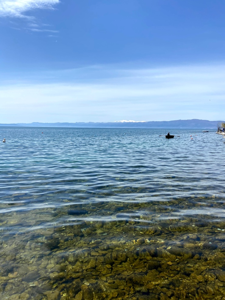 Man in fishing boat on Lake Ohrid. The water is crystal clear and across the lake are snowy mountains of Albania.