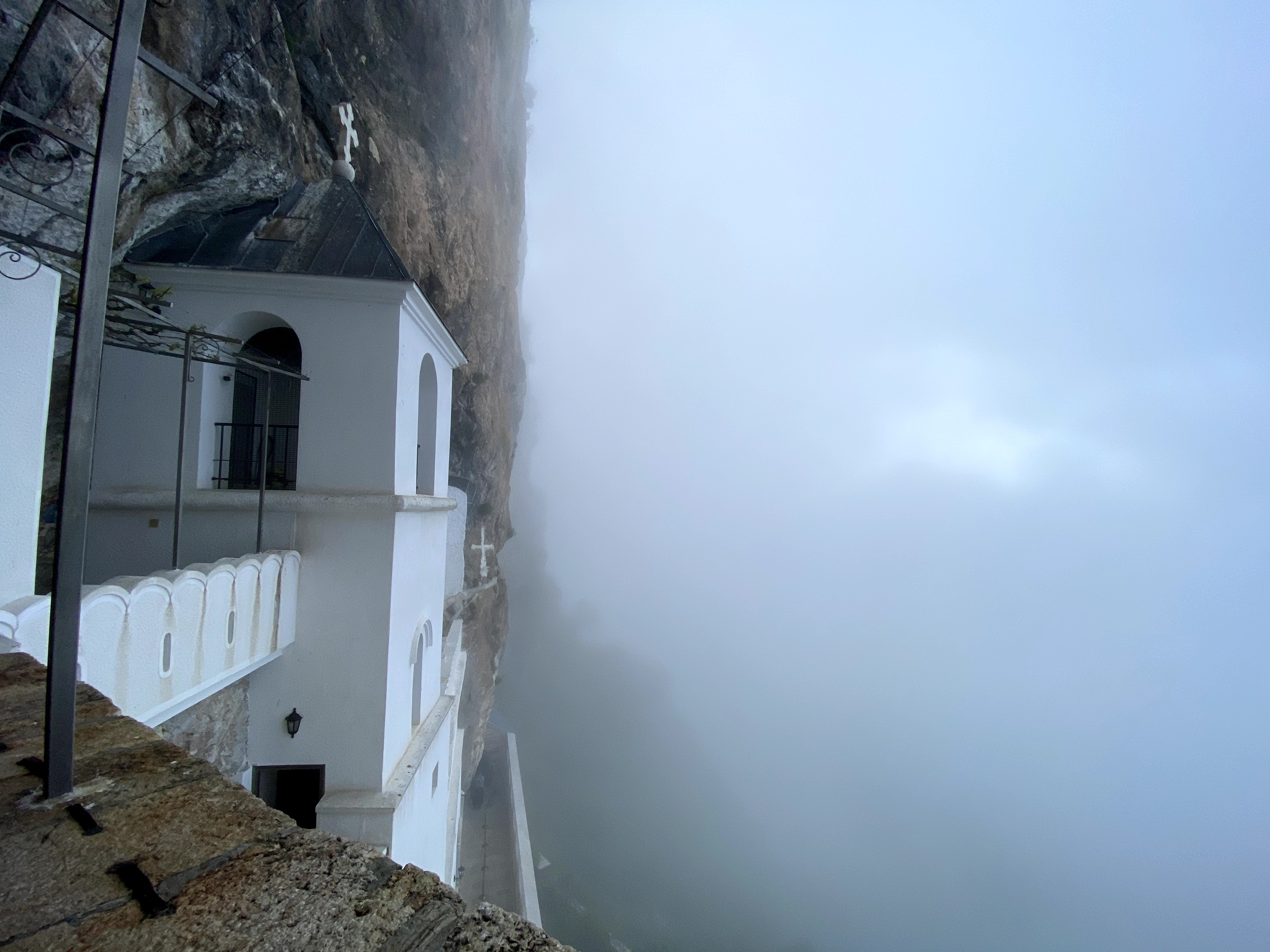 White Church of Ostrog Monastery set into a steep cliff face. Dramatically there is fog covering the view.