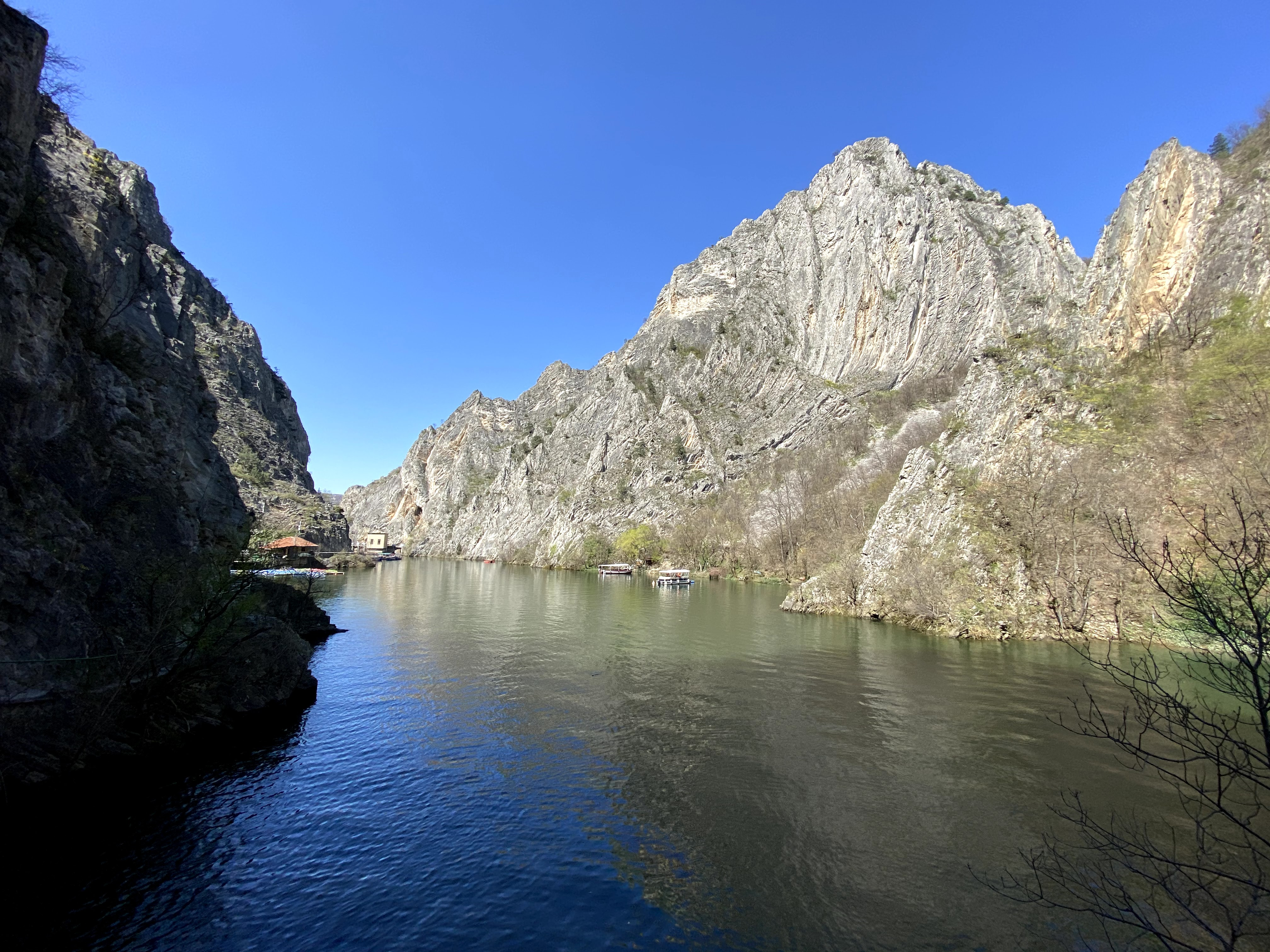 Large open Matka Canyon with a river filled the bottom. There are a few tourist boats on the lake.