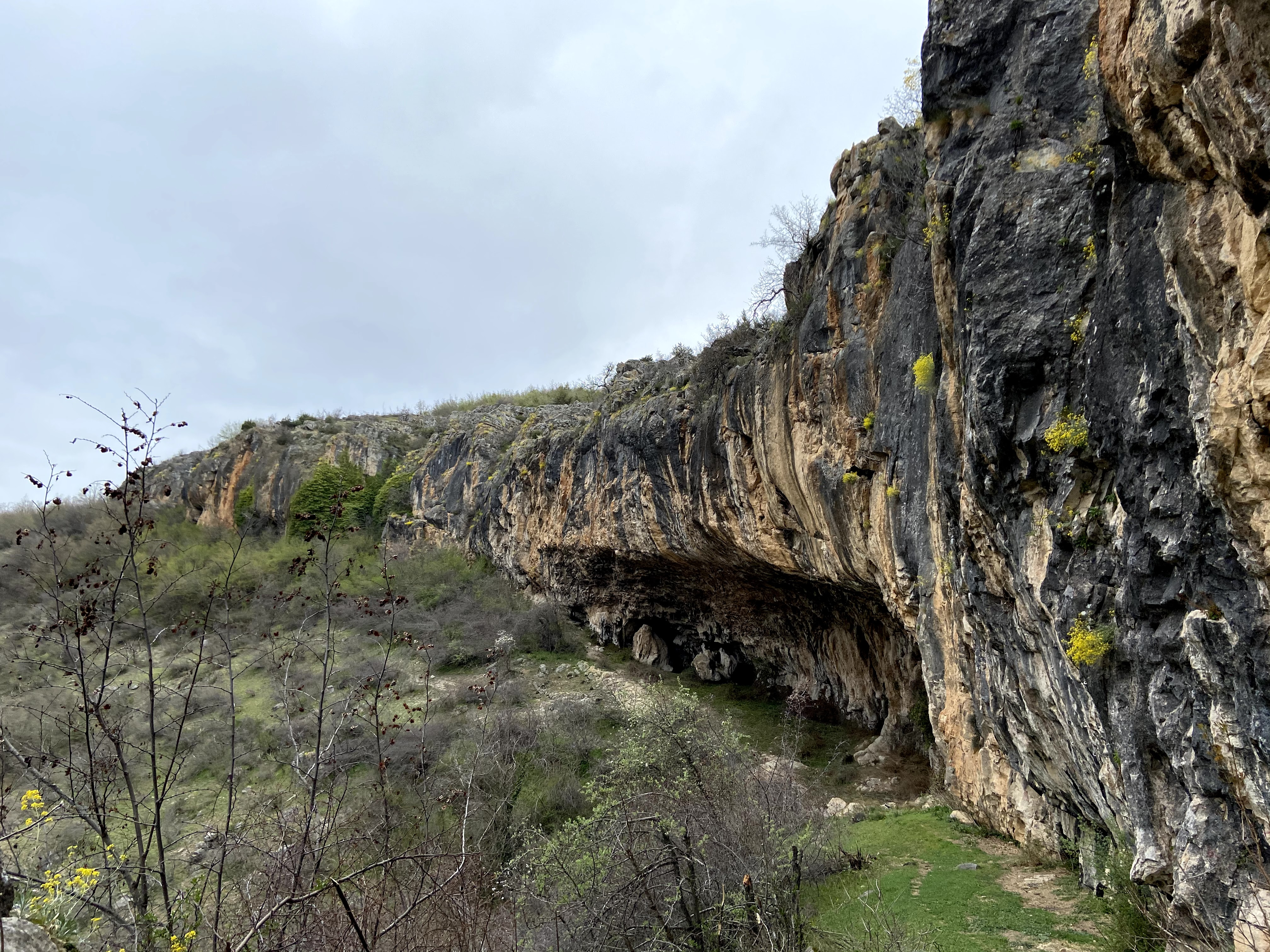 Overhanging cliff of Kadina. There are big strips down the cliff face. In the middle is a large cave with a steep roof that evens out to a short headwall.