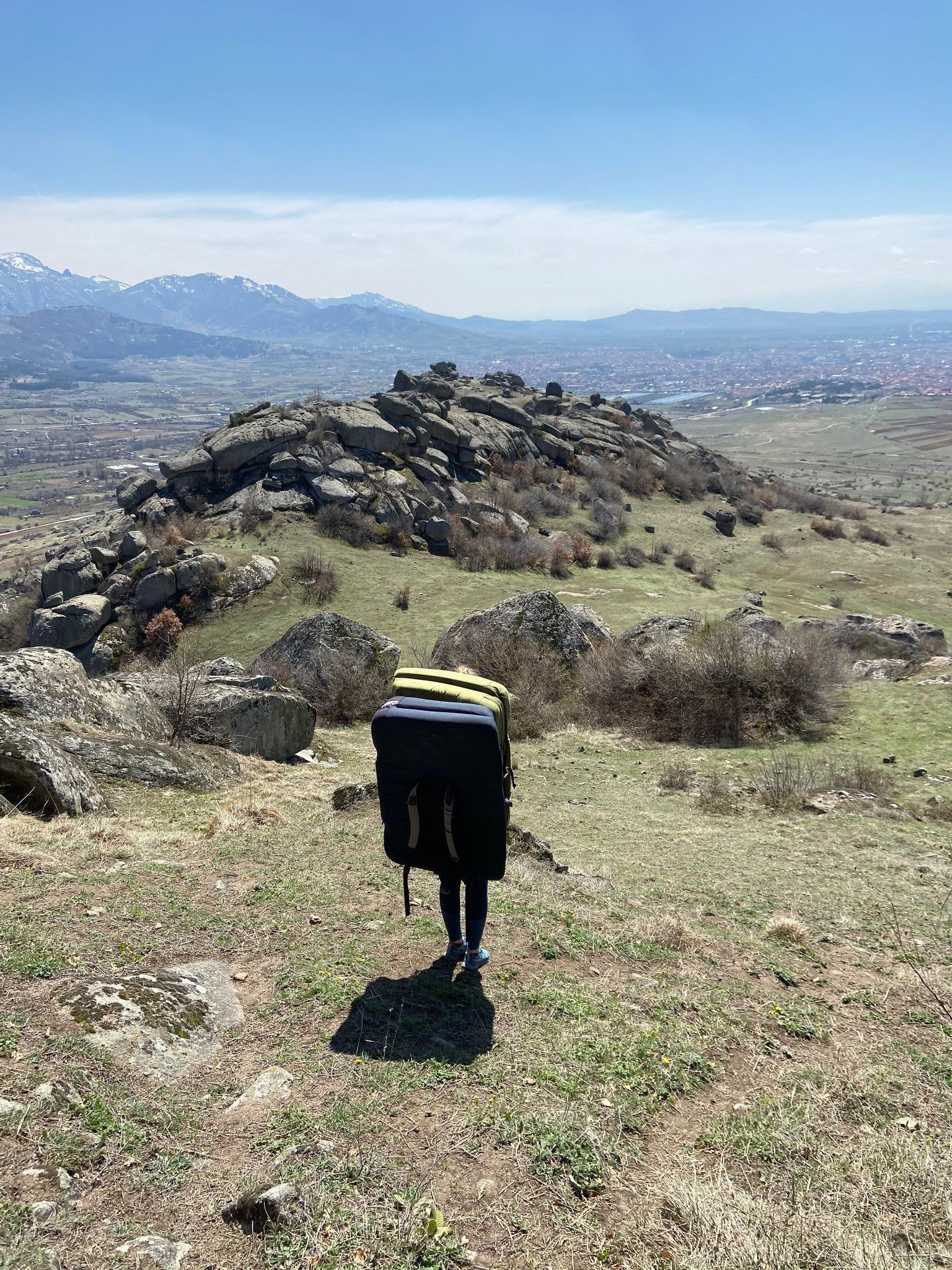 Two bouldering pads strapped together looking out towards a boulder field. The city of Prilep is in the background.