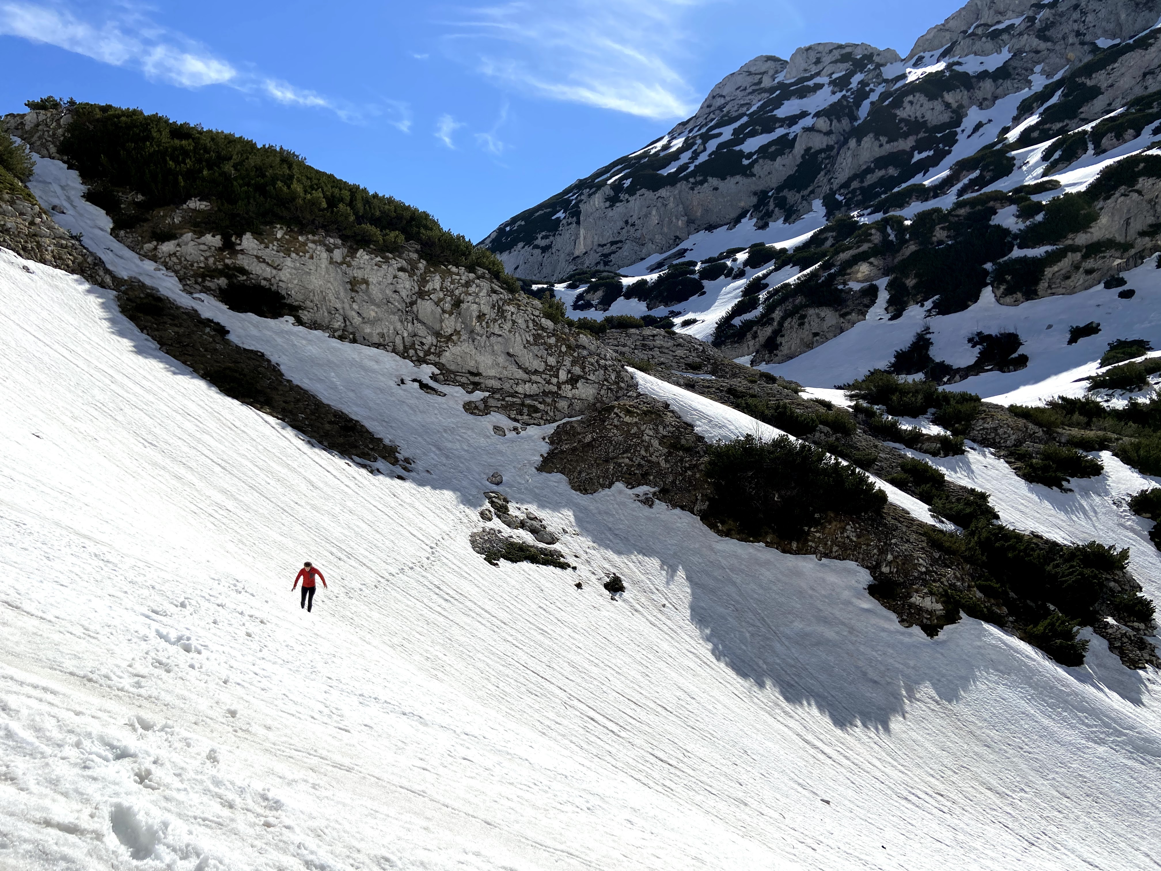 Woman travelling along the deep snow on Bobotov Kuk in Durmitor National Park. There is snow resting on the ledges everywhere.