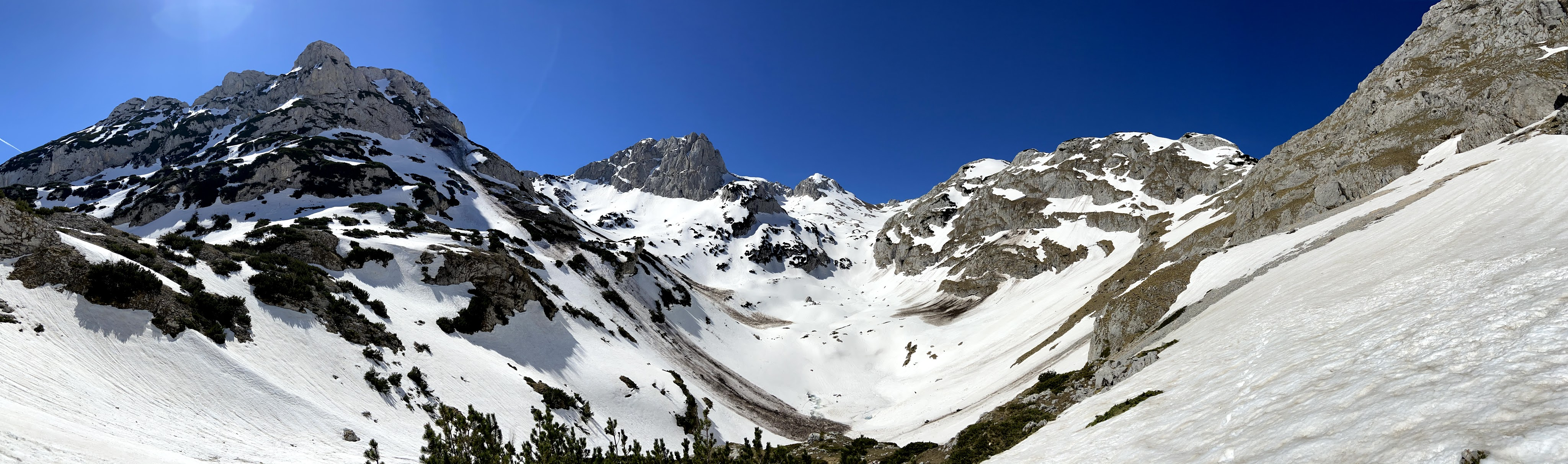 Panoramic photo of the mountain range over in snow. Bobotov Kuk summit is striking. The craggy summit is emerging from the snow.