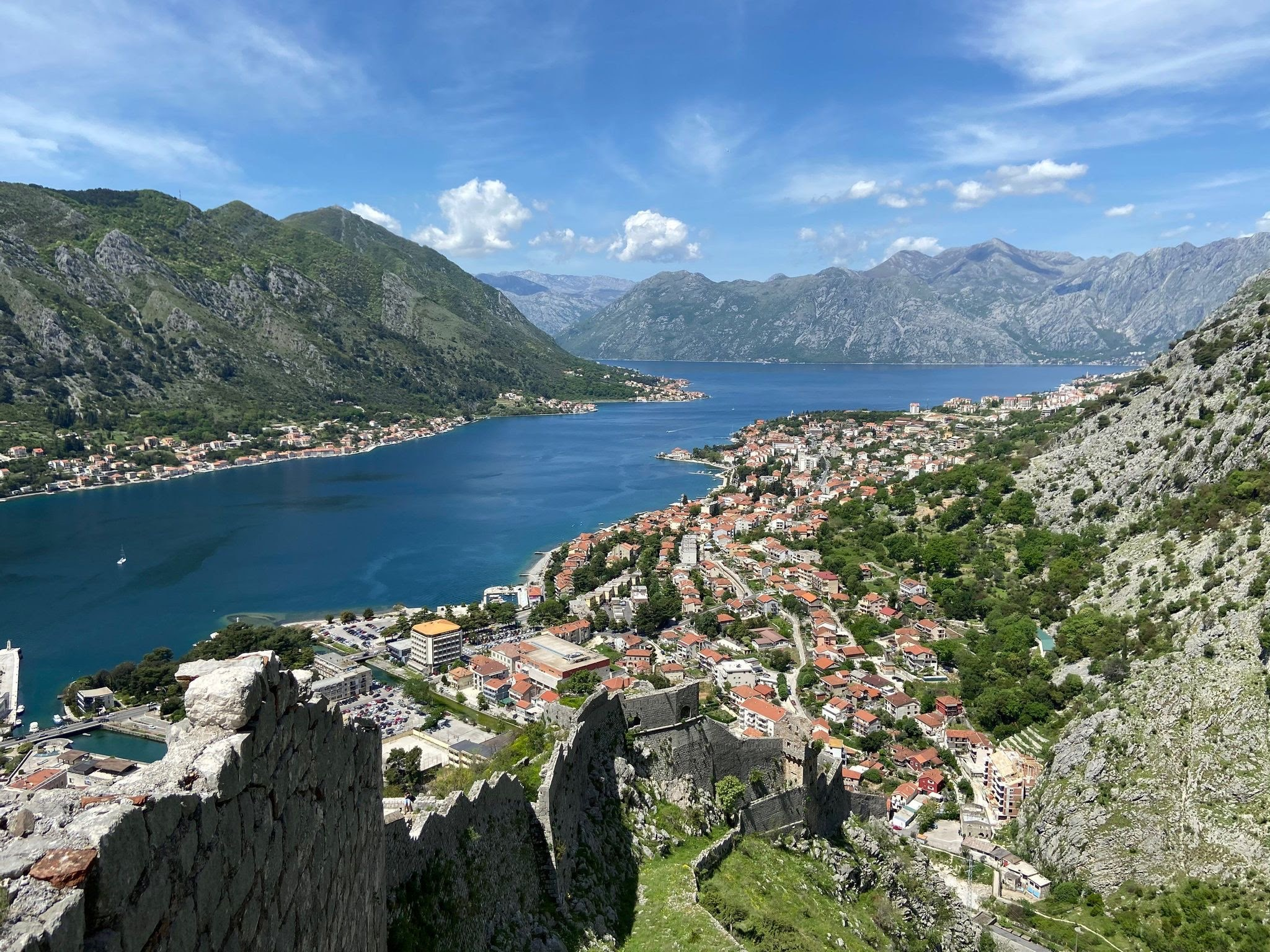 A historic town of Kotor sat in the valley by the water's edge. There are mountains set all around the town with a striking old fortress wall rising from the old town like a spine of a dinosaurs' back.