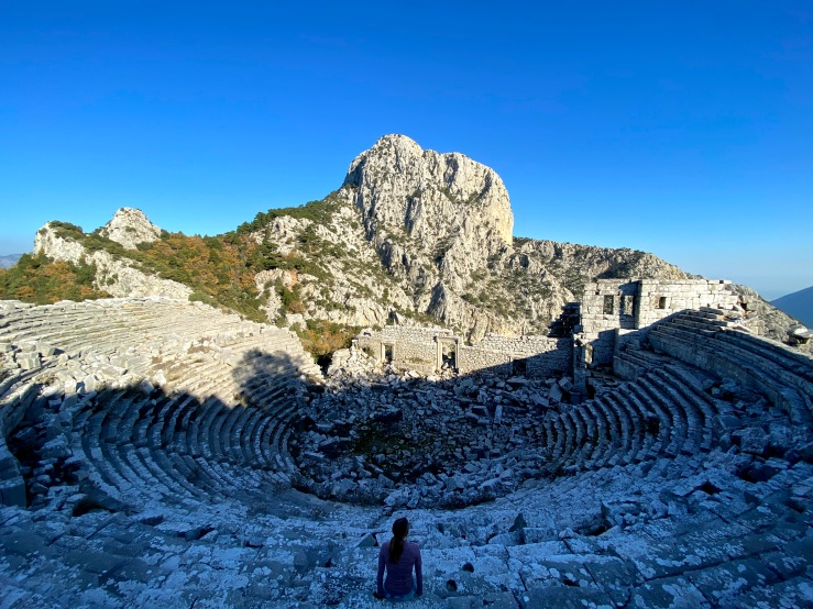 Woman sat in the grand amphitheatre with rock views surrounding.