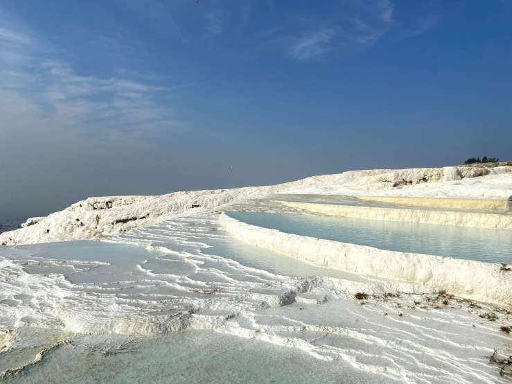 Stark white travertine pools, which looks like snow, filled with clear clear water at Pamukkale.