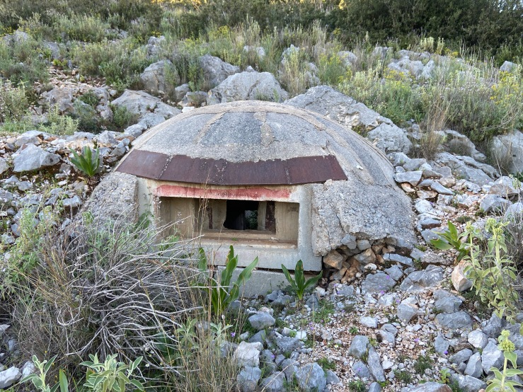 Mushroom shaped concrete bunker set into the rocky ground. There is a small lookout window.