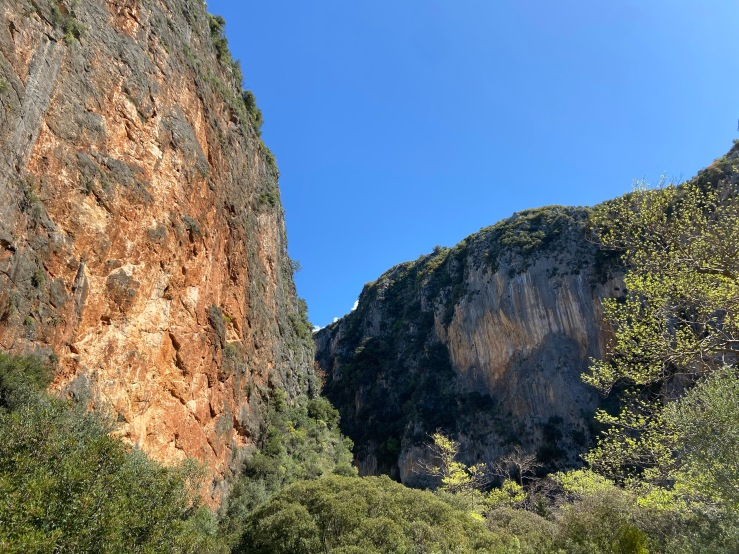 Bright orange limestone rock canyon at Gjipe. With clear blue skies.