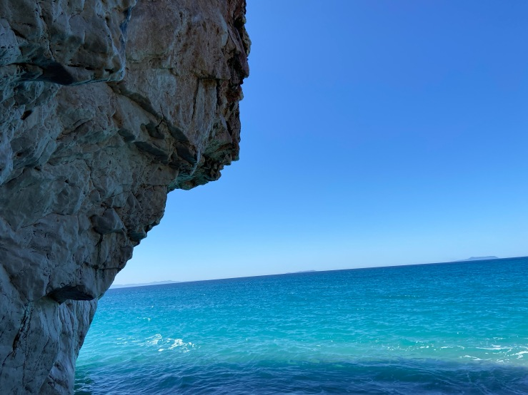 Limestone sea cliff, it is high tide and the water is lapping on the bottom of the crag.